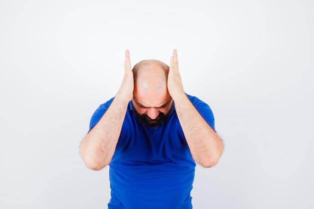 Junger mann, der die hände am kopf hält, während er sich im blauen hemd nach vorne beugt und stressig aussieht, vorderansicht.