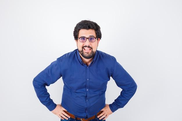 Junger mann, der die hände an der taille in blauem hemd und jeans hält und optimistisch aussieht, vorderansicht.
