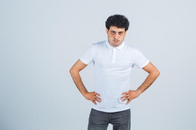 Junger mann, der die hände an der taille in weißem t-shirt, hose hält und boshaft aussieht, vorderansicht.