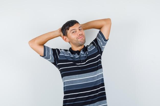 Junger mann, der die hände hinter dem kopf im t-shirt hält und entspannt aussieht, vorderansicht.