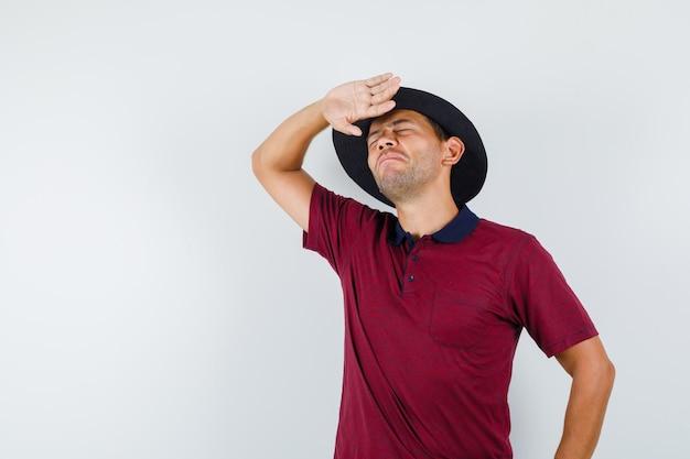 Junger mann, der die hand anhebt, um helle sonne in t-shirt, hut und schwindligem blick zu verhindern, vorderansicht.