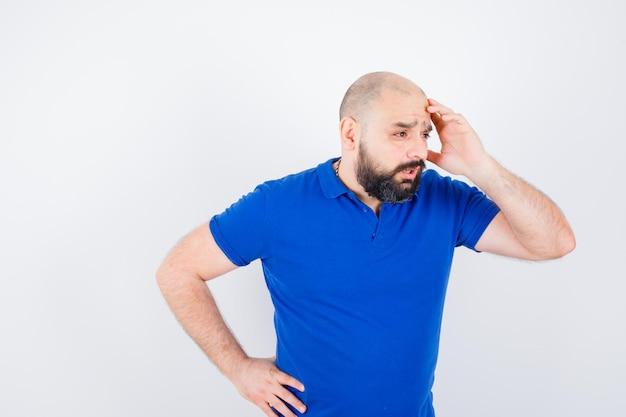 Junger mann, der die hand auf dem kopf hält, während er im blauen hemd spricht und beunruhigt aussieht, vorderansicht.