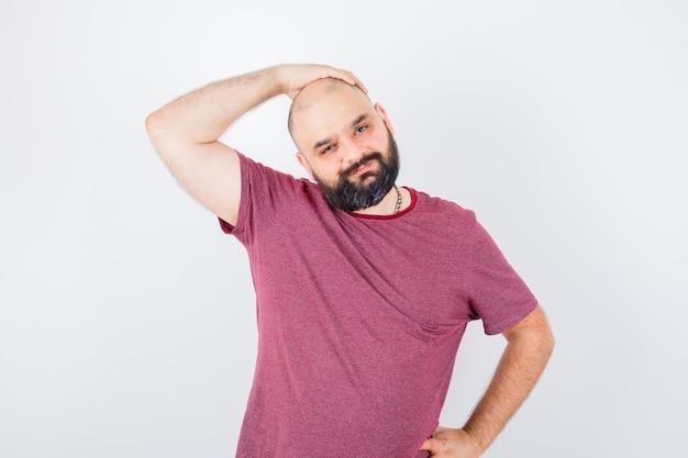 Junger mann, der die hand auf den kopf hält, während er die hand in einem rosa t-shirt auf die taille legt und ernst aussieht. vorderansicht.