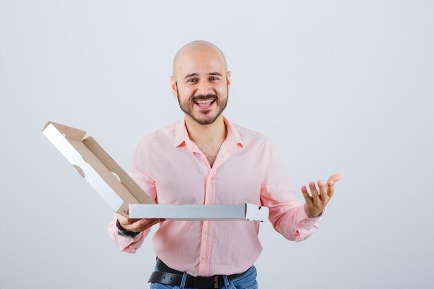 Junger mann, der die hand in fragender geste in hemd, jeans ausdehnt und glückselig aussieht, vorderansicht.