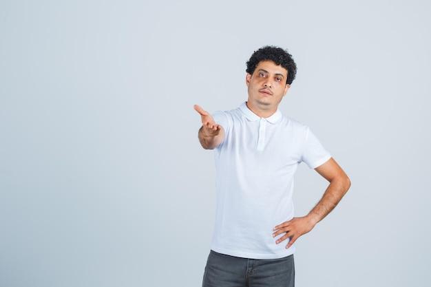 Junger mann, der die hand in verwirrter geste in weißem t-shirt, hose streckt und selbstbewusst aussieht. vorderansicht.