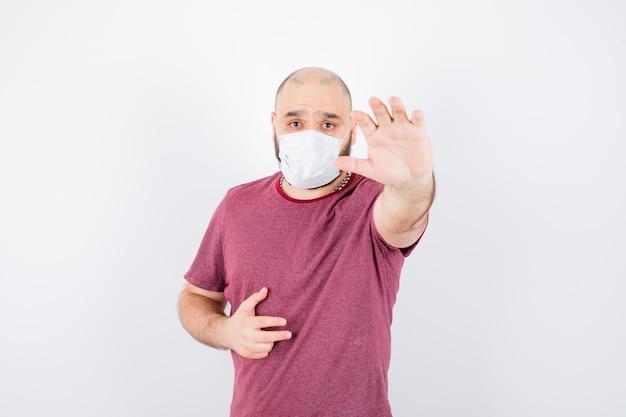 Junger mann, der die hand nach vorne streckt, um hilfe in rosa t-shirt zu erhalten, vorderansicht der maske.