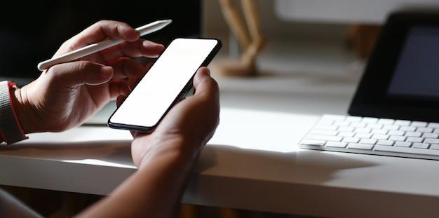 Junger mann, der die ideen vom smartphone des leeren bildschirms sucht
