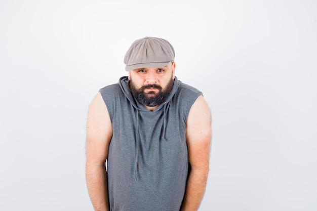 Junger mann, der die kamera in ärmellosem hoodie, mütze und gelangweilt sieht. vorderansicht.