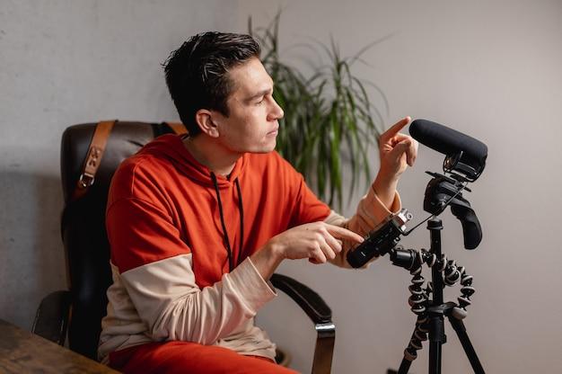 Junger mann, der die kamera und das mikrofon einstellt, um ein video aufzunehmen. vlogger, lehrkonzept.