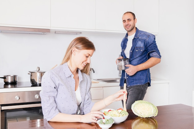 Junger mann, der die lächelnde frau zubereitet salat in der küche zubereitet