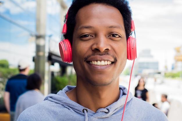 Junger mann, der die musik im freien genießt.