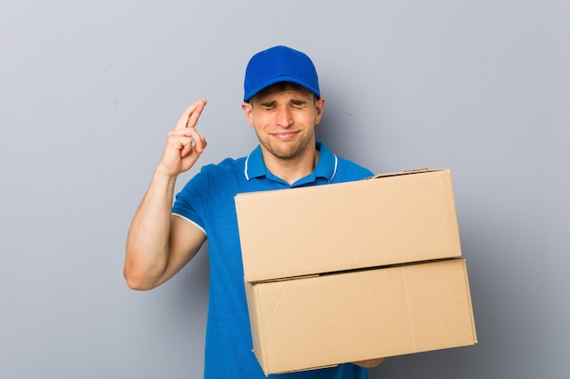 Junger mann, der die pakete kreuzen finger für das haben des glücks liefert