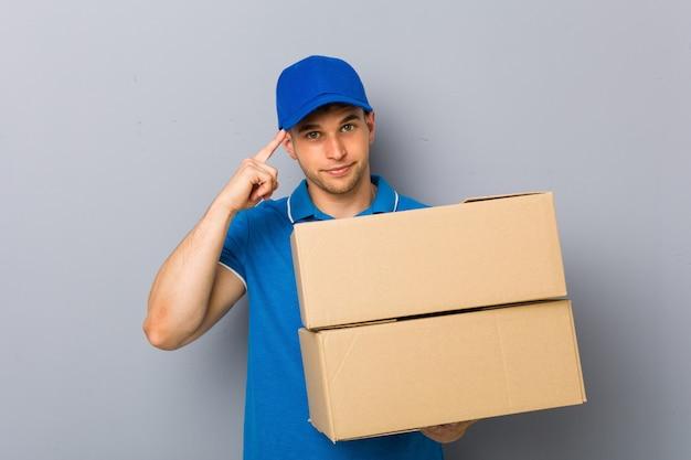 Junger mann, der die pakete zeigen seinen tempel mit dem finger, denkend liefert, konzentrierte sich auf eine aufgabe.