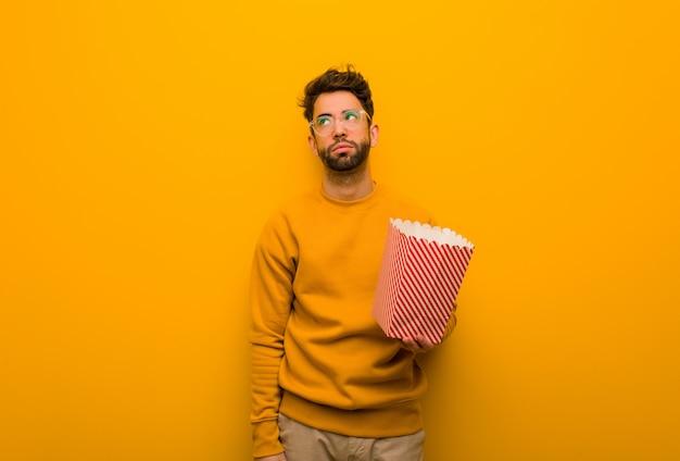Junger mann, der die popcorn müde und gelangweilt hält
