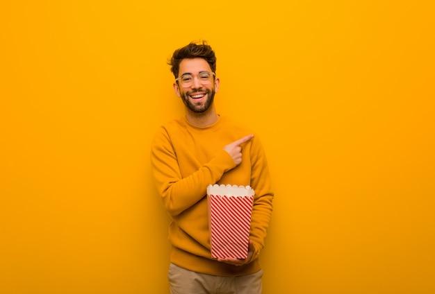Junger mann, der die popcorn zeigt auf die seite mit dem finger hält