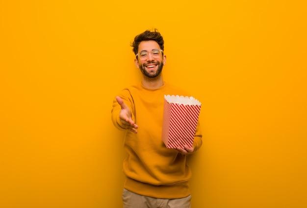 Junger mann, der die popcornholding heraus erreicht, um jemand zu grüßen