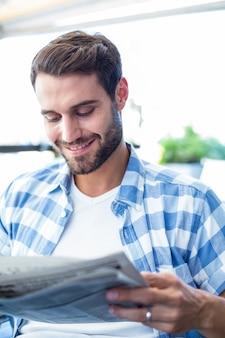 Junger mann, der die zeitungen liest