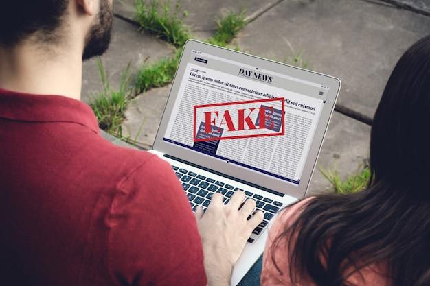 Junger mann, der digitale gefälschte nachrichten auf laptop liest