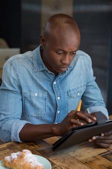 Junger mann, der digitale tablette am holztisch im kaffeehaus verwendet