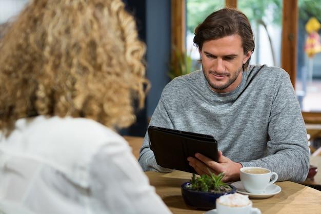 Junger mann, der digitales tablett mit frau im vordergrund am kaffeehaus verwendet