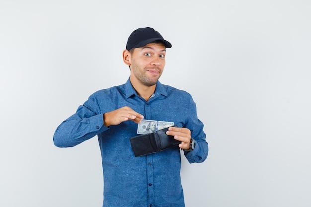 Junger mann, der dollarschein aus der brieftasche in blauem hemd, mütze und fröhlichem blick nimmt. vorderansicht.
