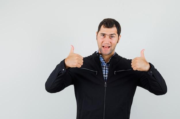 Junger mann, der doppelte daumen oben im hemd, in der jacke zeigt und selbstbewusst, vorderansicht schaut.
