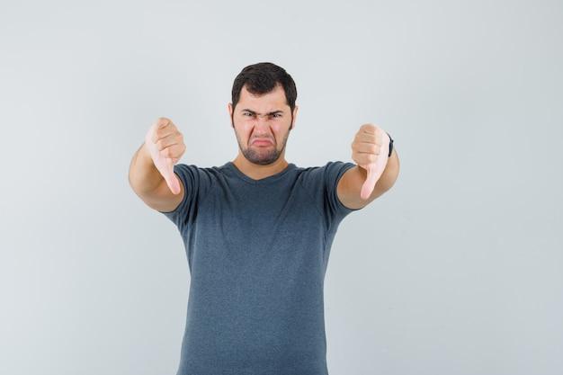 Junger mann, der doppelte daumen unten im grauen t-shirt zeigt und unzufrieden aussieht, vorderansicht.