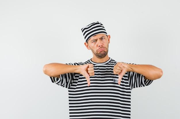 Junger mann, der doppelte daumen unten in gestreiftem t-shirt, hut zeigt und enttäuscht aussieht.