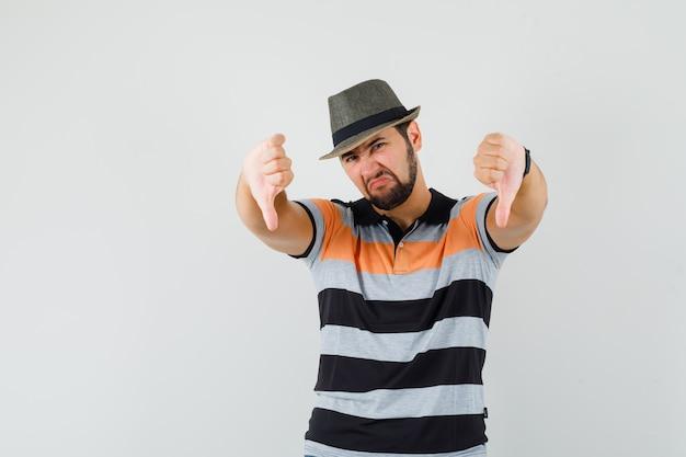 Junger mann, der doppelte daumen unten in t-shirt, hut zeigt und unzufrieden aussieht