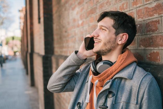 Junger mann, der draußen am telefon spricht.