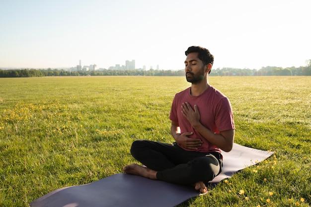 Junger mann, der draußen auf yogamatte meditiert