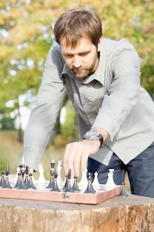 Junger mann, der draußen im sonnenschein steht, sich nach vorne lehnt und eine bewegung in einem schachspiel macht