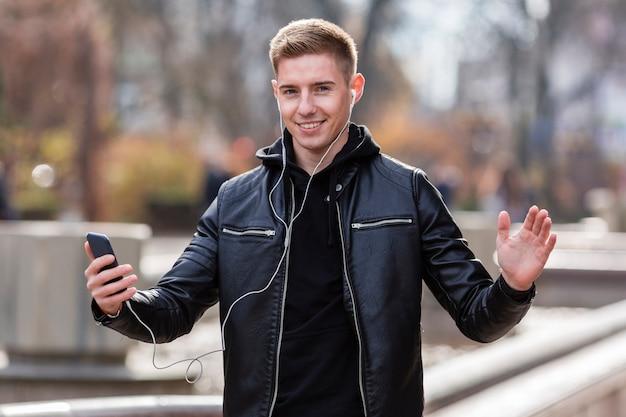 Junger mann, der draußen musik auf kopfhörern hört