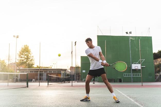 Junger mann, der draußen tennis spielt