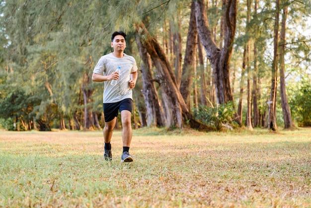 Junger mann, der draußen training den park rüttelt und tut