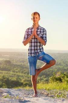 Junger mann, der draußen yoga im sonnengesundheitskonzept tut