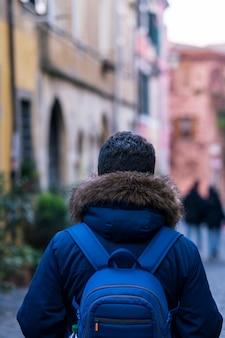 Junger mann, der durch alte straßen in der alten stadt geht