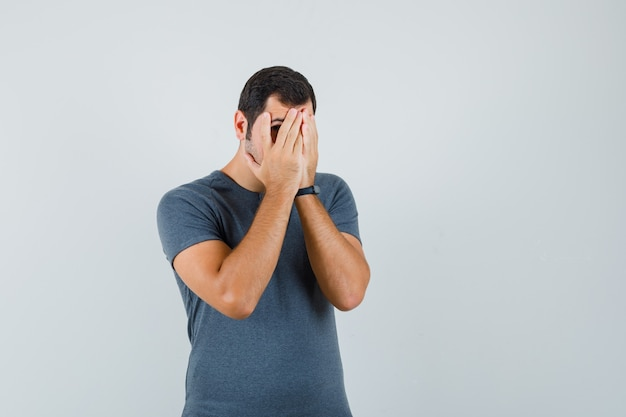 Junger mann, der durch finger im grauen t-shirt schaut und ängstlich schaut. vorderansicht.