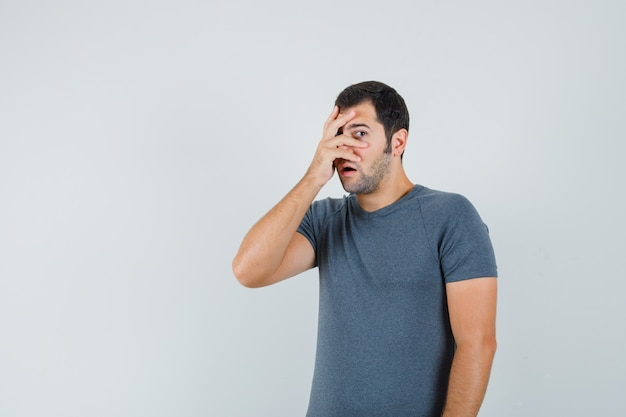 Junger mann, der durch finger im grauen t-shirt schaut und ängstlich schaut