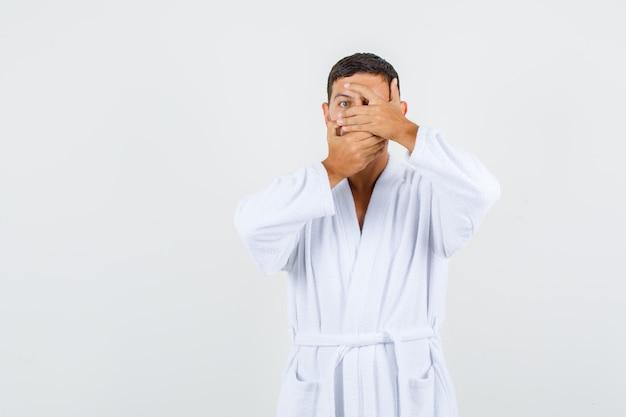Junger mann, der durch finger schaut, während mund im weißen bademantel bedeckt und ängstlich schaut. vorderansicht.