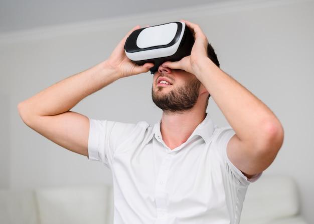 Junger mann, der durch gläser der virtuellen realität schaut