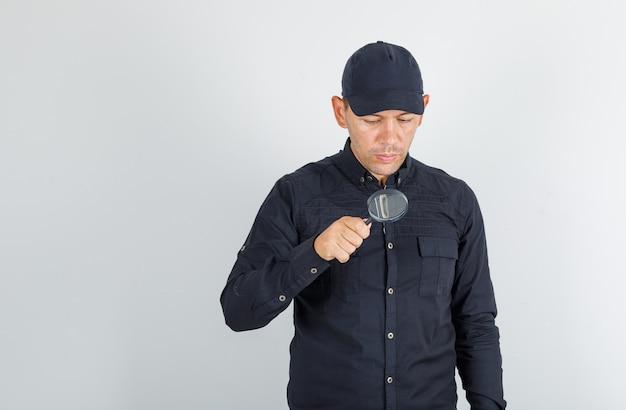 Junger mann, der durch lupe im schwarzen hemd mit kappe schaut