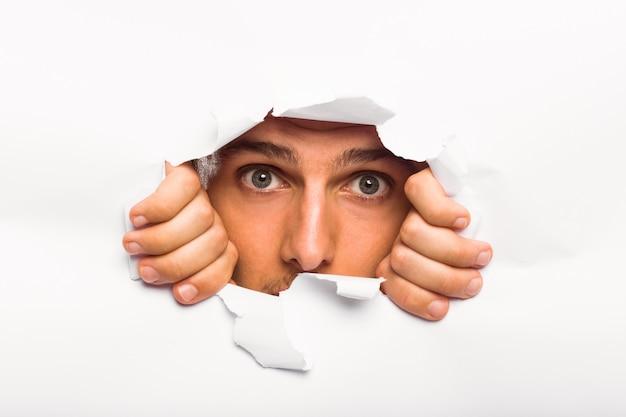 Junger mann, der durch papierriss schaut