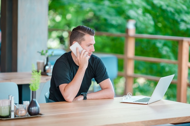 Junger mann, der durch smartphone in trinkendem kaffee des cafés im freien spricht. mann mit mobilen smartphone.