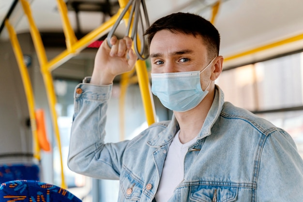 Junger mann, der durch stadtbus reist, der chirurgische maske trägt