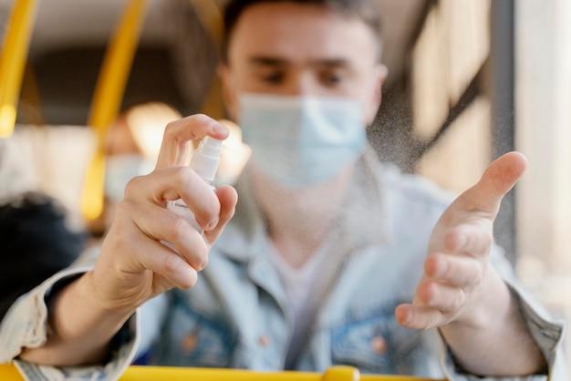 Junger mann, der durch stadtbus reist, der seine hände mit desinfektionsgel desinfiziert