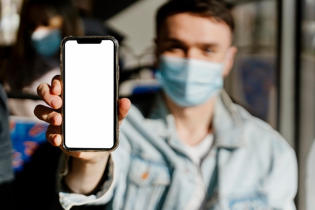 Junger mann, der durch stadtbus reist, der smartphone mit leerem bildschirm zeigt