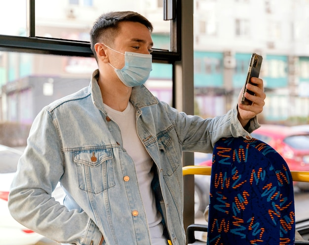 Junger mann, der durch stadtbus unter verwendung des smartphones reist