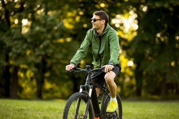 Junger mann, der e-bike in der natur reitet