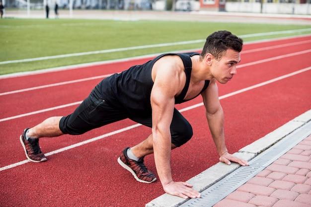 Junger mann der eignung, der liegestütz auf rennstrecke tut